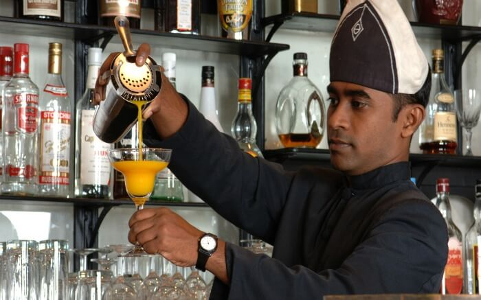 A bartender prepares a drink for guests at Le Garage nightclub