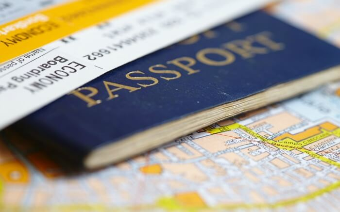 Passport and flight tickets lying on a map