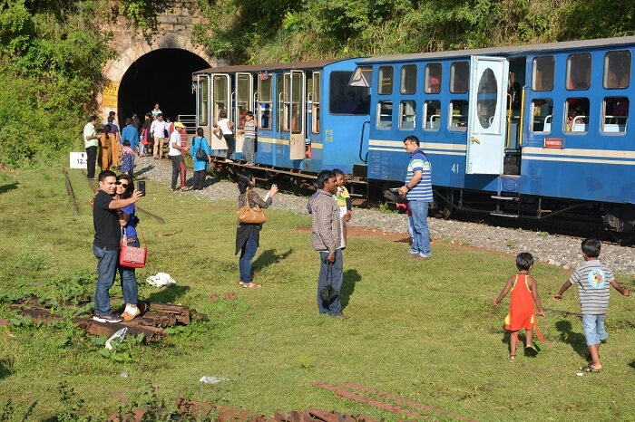 Tourists in front of the famous toy train in Mettupalayam