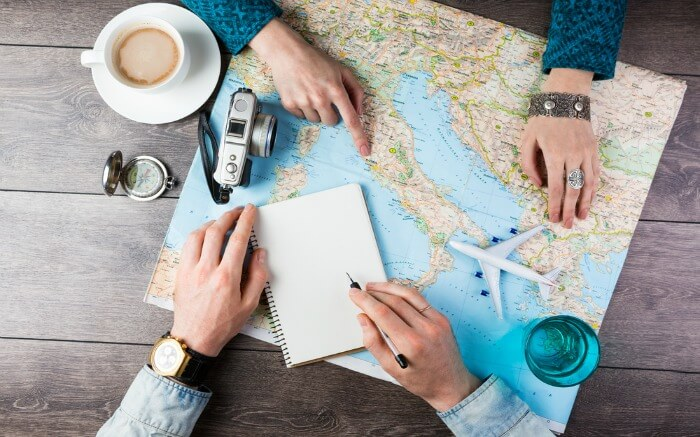 A man and woman planning a trip with a map