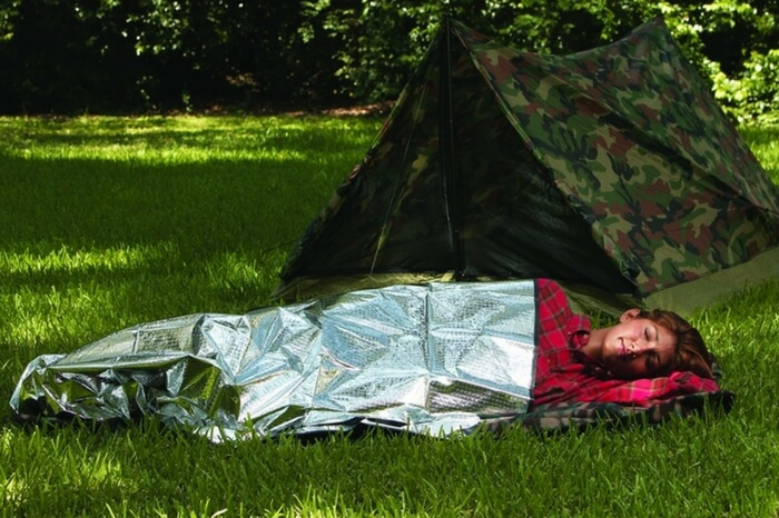 A traveler sleeping in a thermal blanket