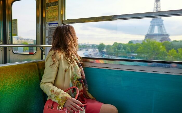 A woman traveling train going past the Eiffel Tower in Paris