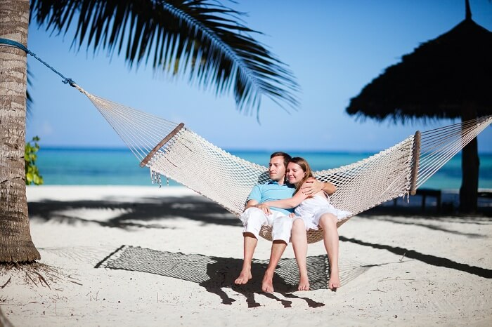 Young romantic couple relaxing in hammock on tropical beach of Zanzibar island