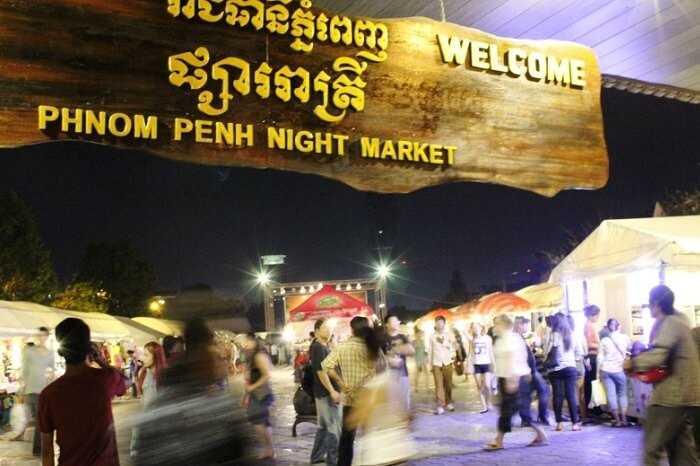 Tourists and locals walking through the Phnom Penh night market in Cambodia