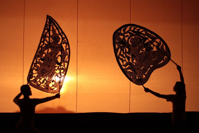 Two artists seen as shadows during one of the shadow puppetry performance in Cambodia