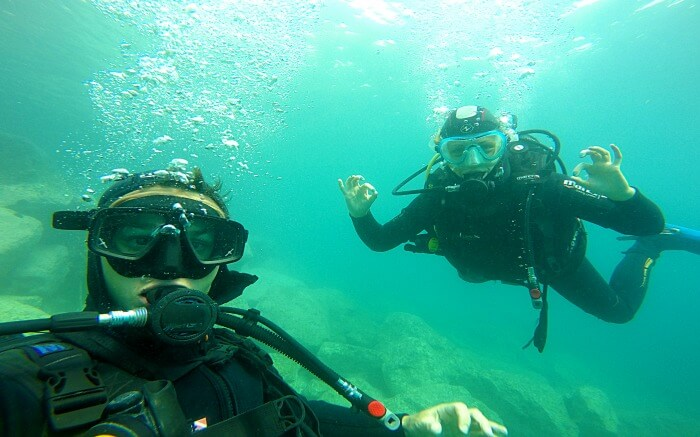 Two divers posing for photograph inside the ocean