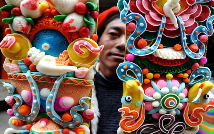 A man holding Buddhist butter sculpture which is a highlight of Tibetan losar decoration