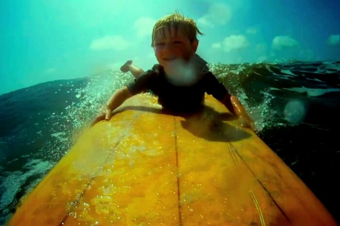 Child playing on waves in a still from the movie Life in a Day