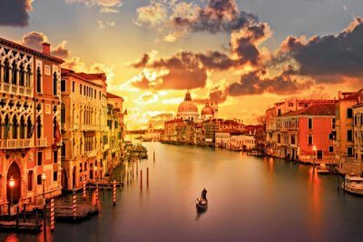 Man sailing a boat into the sunset in Grand Canal in Venice