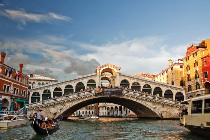 A boat sailing towards the arc of Rialto Bridge in Venice