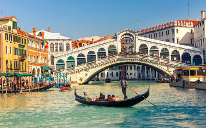People enjoying Gondola ride - which is considered one of the top things to do in Venice