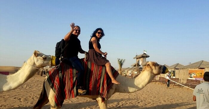 Roshan and his wife riding a camel in Dubai