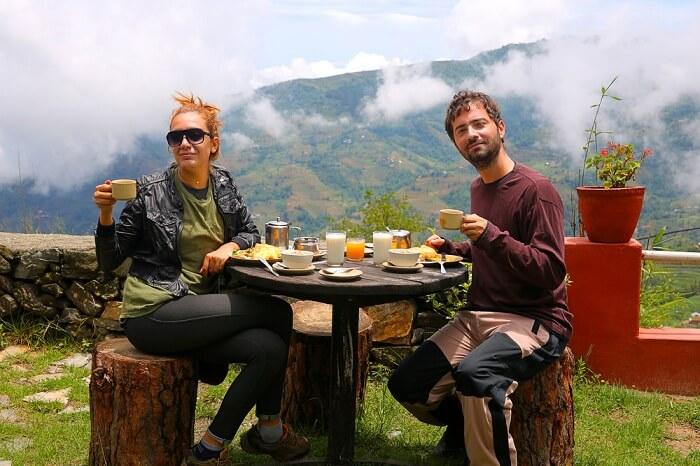Tourist couple on a Nepal honeymoon eating breakfast in at Nagarkot