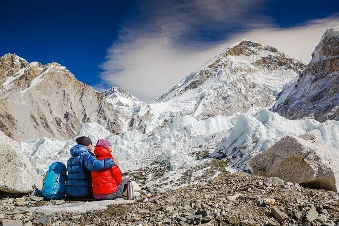 An adventurous couple enjoying the mountain view while trekking in Nepal