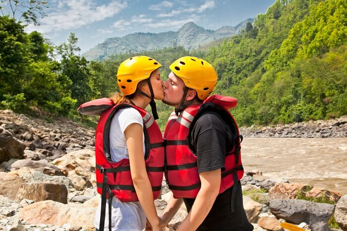 Man and woman kissing for good lack before river rafting during their honeymoon in Nepal