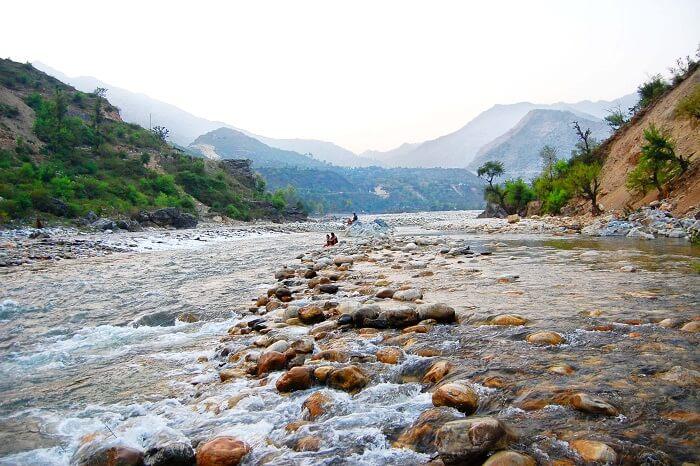 Tourists enjoying the flowing river at Chakrata