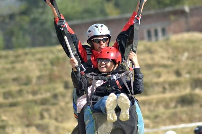 A girl landing after her paragliding adventure
