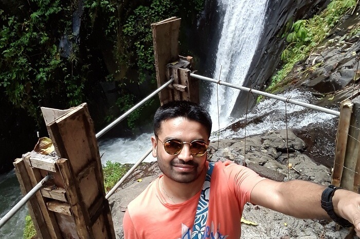 A man taking a selfie near a waterfall