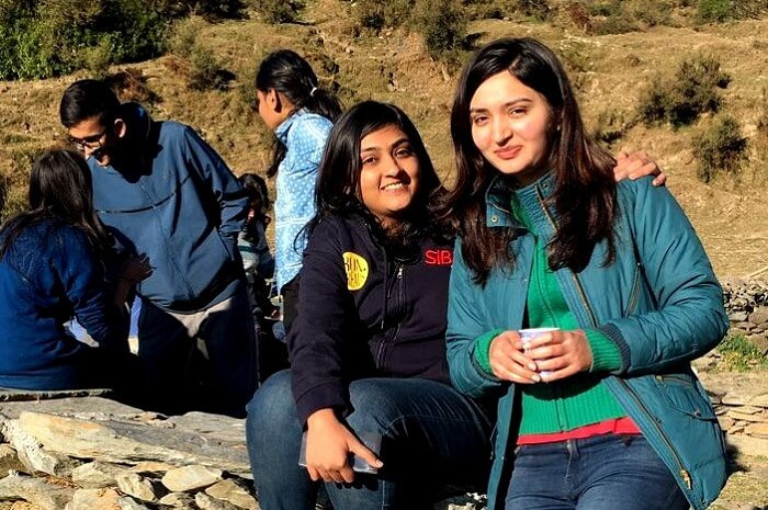 Two girls getting their picture clicked on a trip