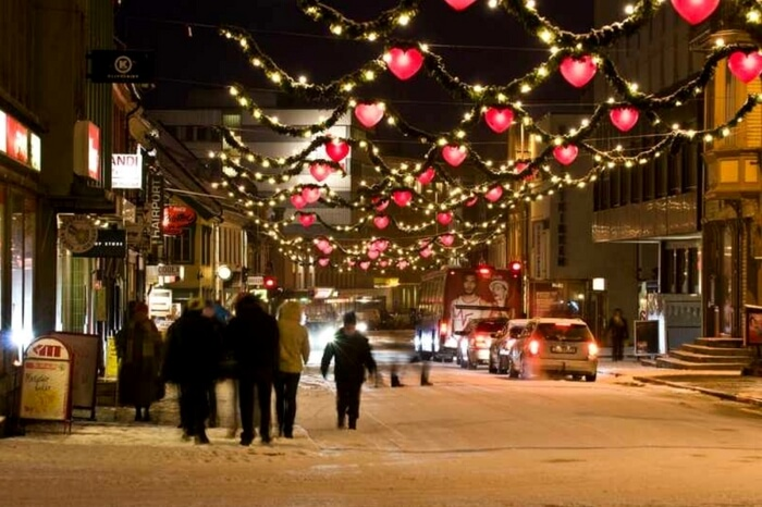People in Tromso walk past a decorated street during Christmas