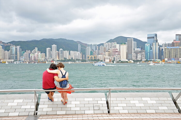 A honeymoon couple in Hong Kong sits at a waterfront