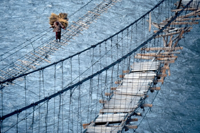 A man crossing the dangerous Hussaini Hanging Bridge in Pakistan