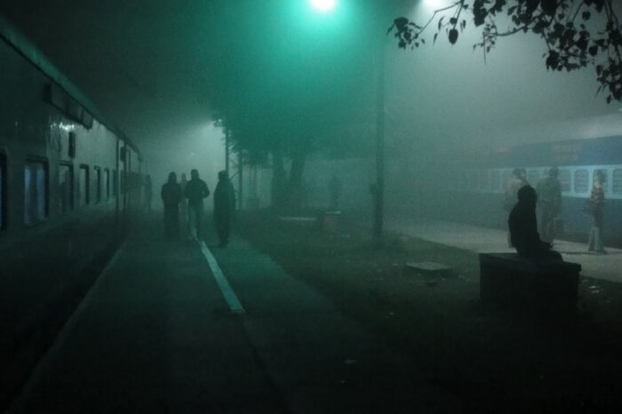 Train at a station on a foggy night