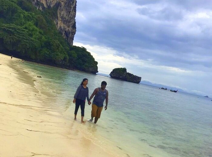Jegen and his wife take a walk on a beach of Thailand