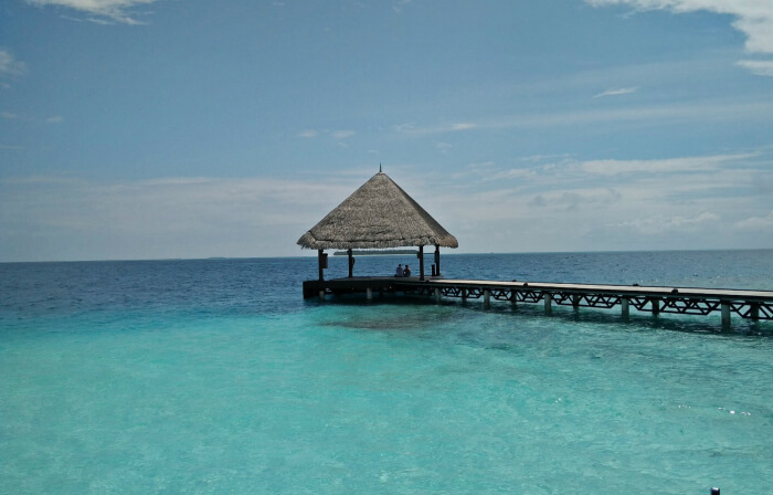 thatched huts in maldives resort and serene blue waters beyond