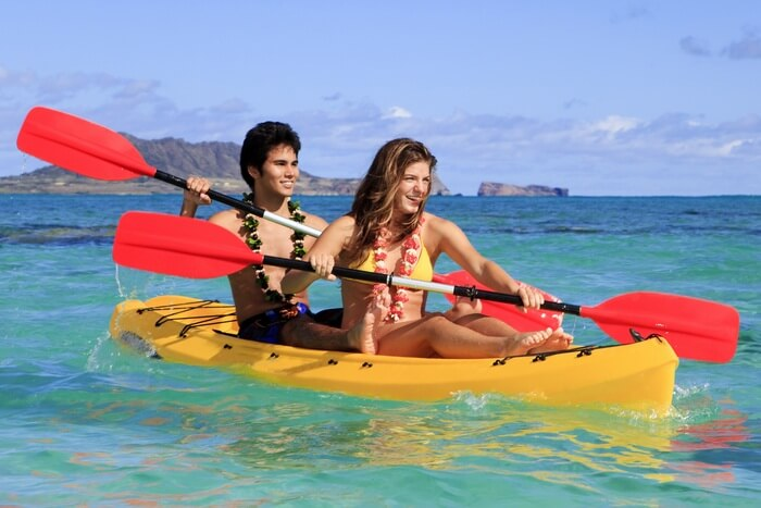 A couple kayaking in the sea at Kauai island on their Hawaii honeymoon