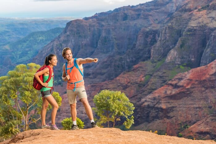 Hiking couple looking at view in mountain nature during hike in Waimea Canyon State Park on the Kauai island in Hawaii