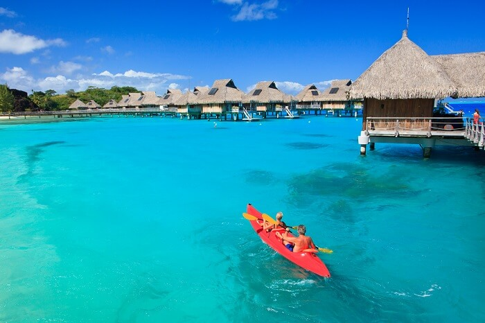 A couple kayaking near the overwater villas in Bora Bora