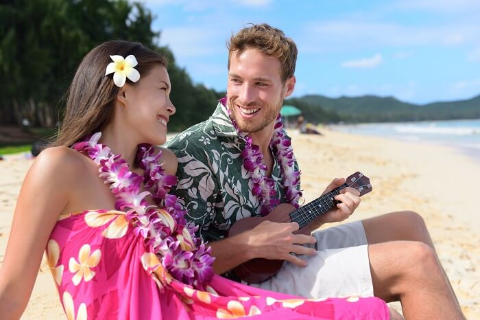 A couple relaxing on a sandy beach of Hawaii