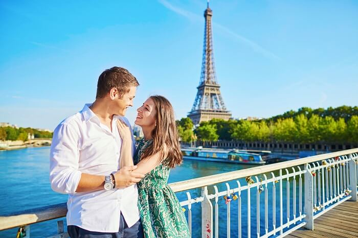 A couple on a bridge with the Eiffel Tower in the background