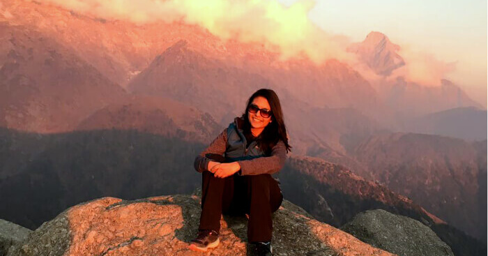 Tejal sitting on a cliff during her weekend trip to Mcleodganj