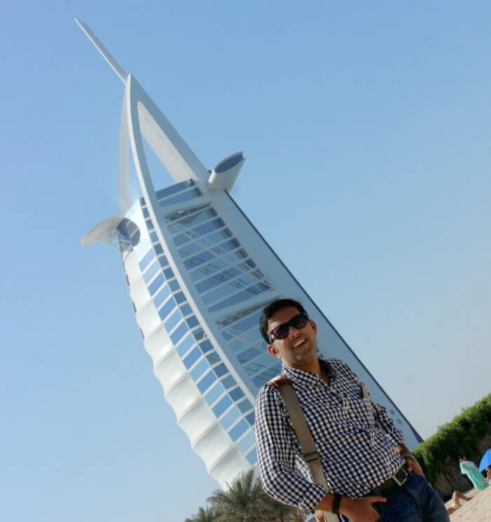 Standing before the grand Burj Al Arab hotel in Dubai