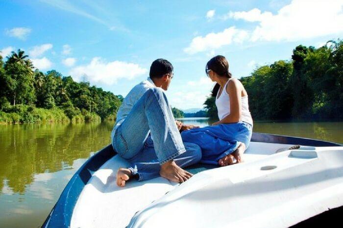Couple enjoying a boat ride across Mahaveli river Sri Lanka