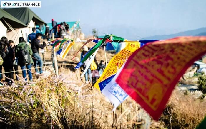 Prayer flags with camps in the background in Kanatal