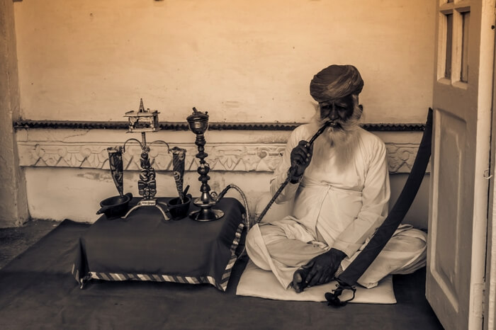 Man smoking pipe inside Mehrangarh Fort