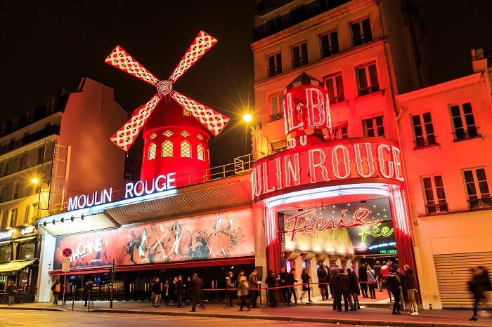 Tourists stand in a queue to enter the Moulin Rouge night cabaret