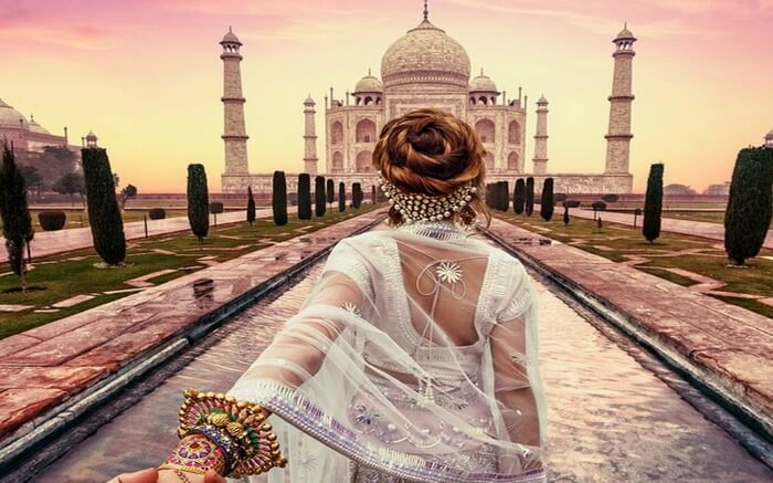 A woman posing in front of Taj Mahal
