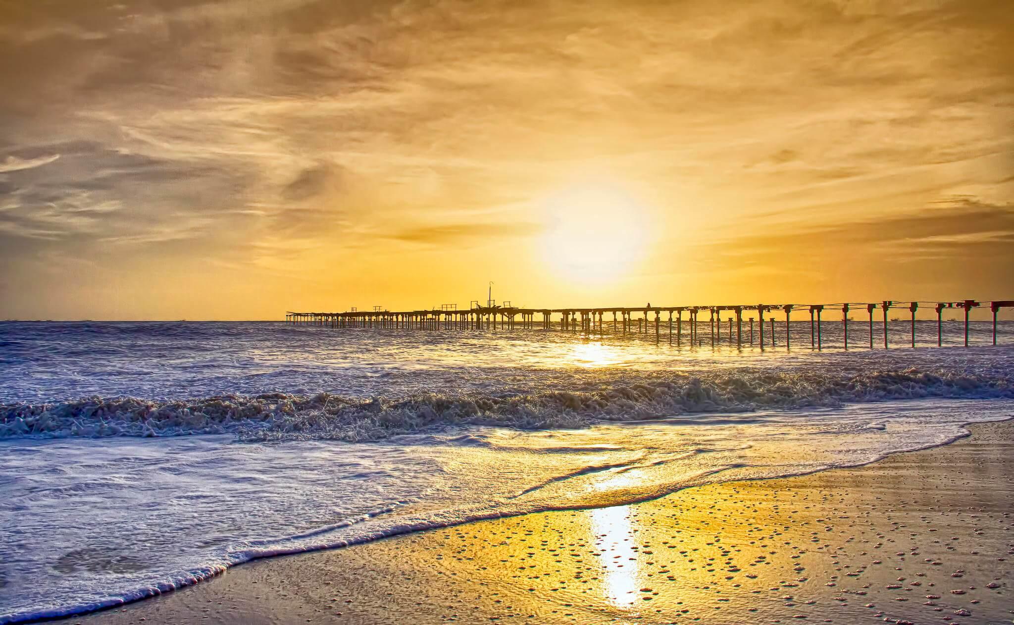 sunset behind a pier at Alleppey beach