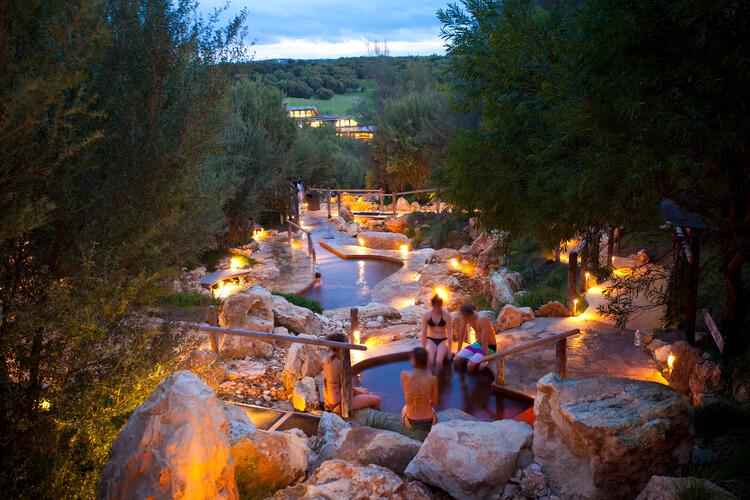 men and women taking bath in Peninsula hot spring at night