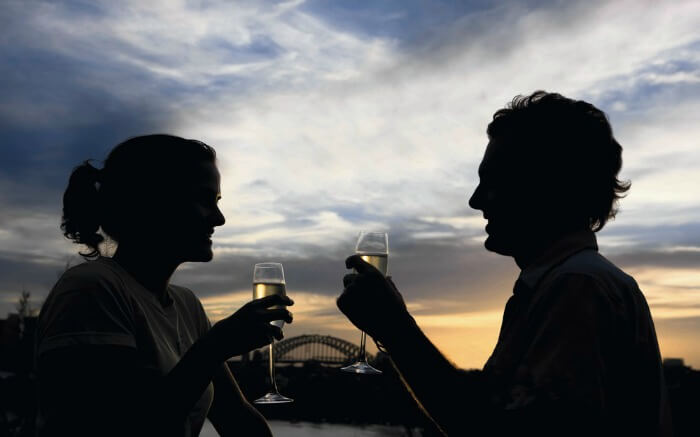A couple enjoying wine with Sydney Harbour in background