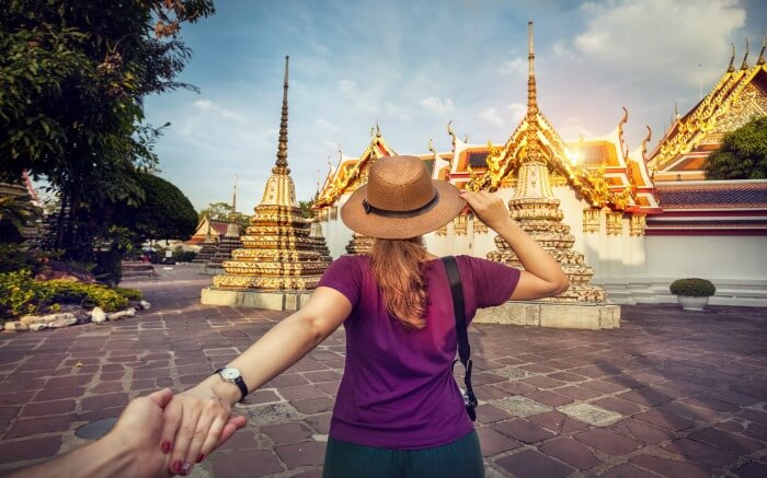 A woman in hat posing in front of Wat Pho