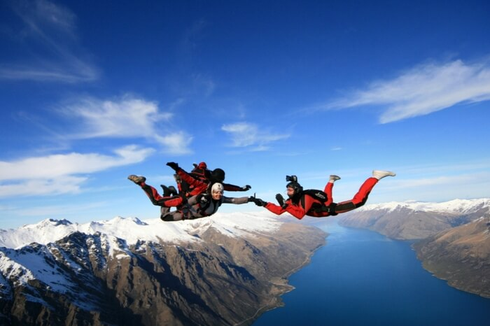 Two professional skydivers accompany an adventurer while skydiving in New Zealand