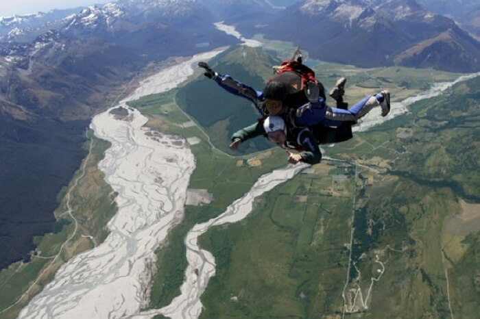 Adventurers skydiving in Glenorchy region in New Zealand