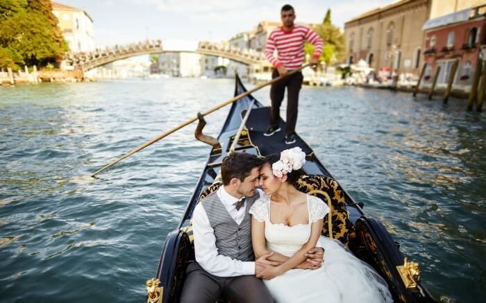 A couple in a venetian Gondola in Italy