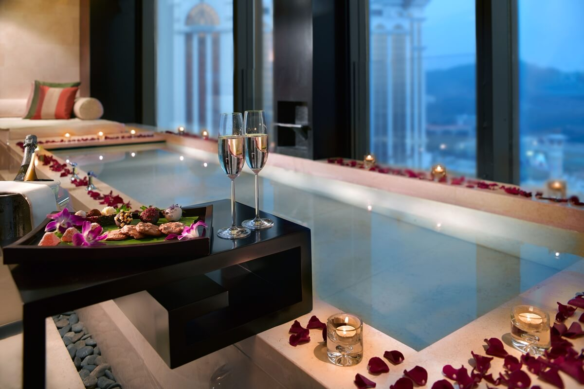 two champagne glasses and bathtub decorated with rose petals