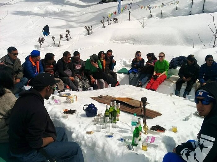 A group of campers having a meal outside the igloo in Manali